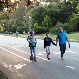 a family walking and scooting on car-free JFK Drive