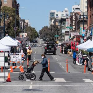 Photo of a street closed in the Tenderloin during summer 2021 with vendors and pedestrians