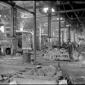 A view inside the overhaul shop in 1912 showing a row of streetcars at left and staff tearing down trucks and motors at right.