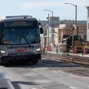 L Taravel bus passes construction of rails on Taraval Street