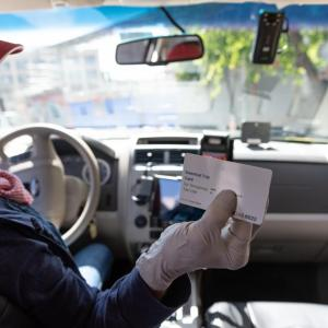 Image of taxi driver holding essential trip card